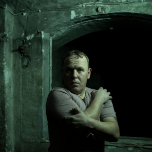 A man stands holding himself in a darkened prison cell