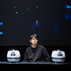 A man sits on stage at a desk with two rice cookers on either side