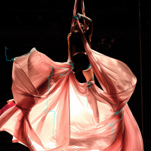 An aerialist hangs draped in pink fabric