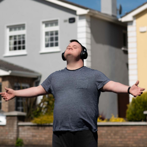A man wearing headphones stands in a suburban estate with his arms outstretched