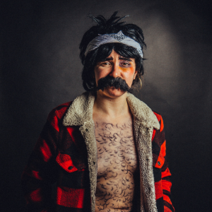 Natalie/Nate stands in a tartan jacket, wig and moustache with hair drawn on their chest