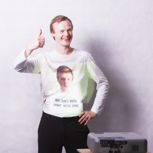 A man stands smiling with his thumb up, a projector projects the words 'we don't know what we're doing' onto his white jumper