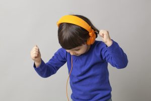 happy young child dancing in listening to music