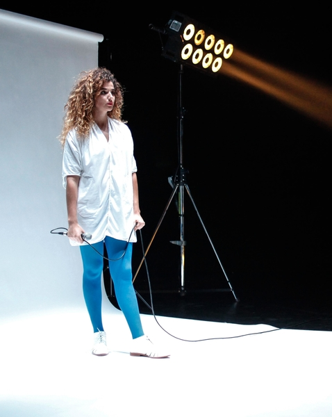 Show Image; Collection of Lovers Co-Created by António Pedro Lopes, Bernardo de Almeida and Raquel André, presented at Dublin Theatre Festival. A woman stands in a photography studio looking off screen, she holds a microphone