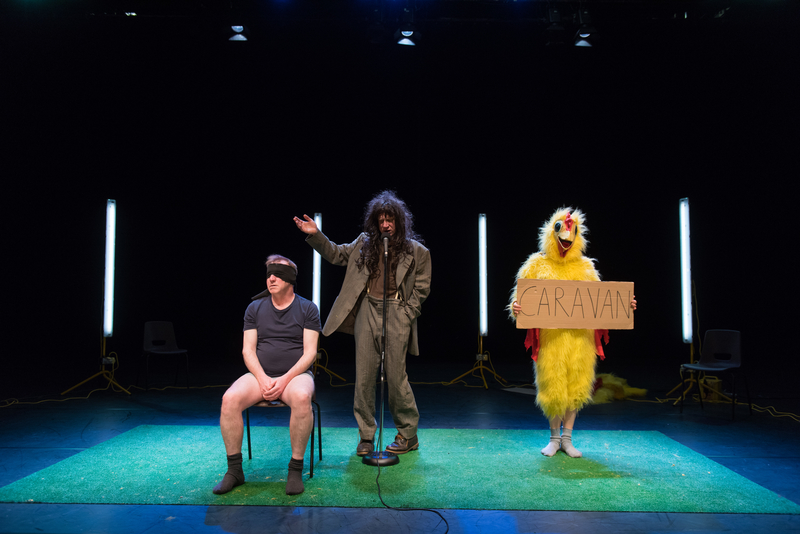 Show Image; Real Magic, conceived of and devised by Forced Entertainment company members, Directed by Tim Etchells presented at Dublin Theatre Festival. 3 characters in a sparse stage space; a blindfolded man without trousers sits on a chair, a dishevelled man in a grey suit and long brown wig gestures & speaks into a microphone in the centre. To the right of him a person in a chicken suit holds a cardboard sign saying Caravan