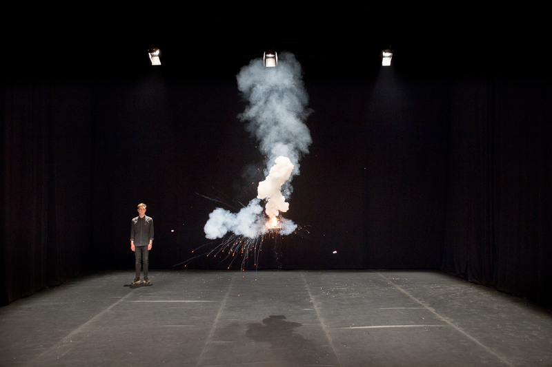 Show Image; Physics and Phantasma, theatre written & performed by Iggy Long Malmborg presented as part of Dublin theatre Festival. Iggy stands in the back of an empty black theatre space. An apparition of fire and smoke floats in the centre stage area