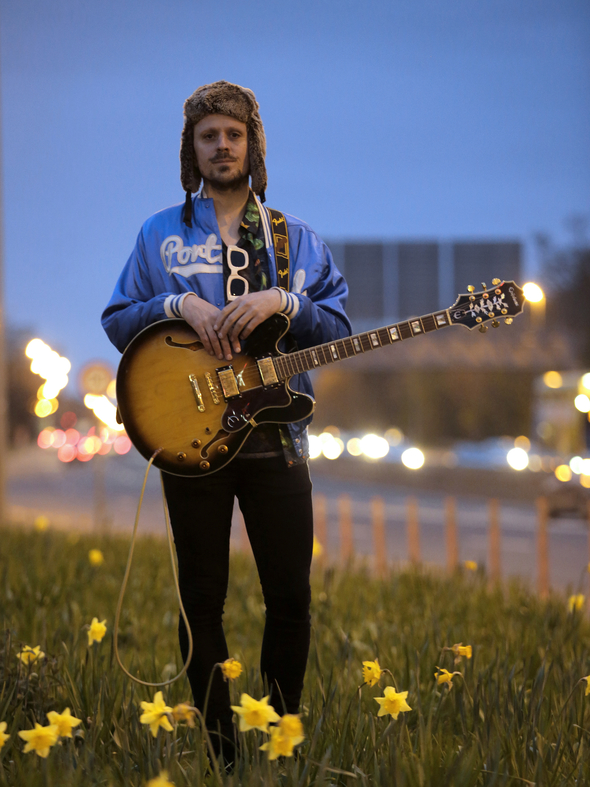 Bluffers Guide to Suburbia, theatre written and composed by Ray Scannell as part of Dublin Theatre Festival. Ray stands near a motorway with his guitar